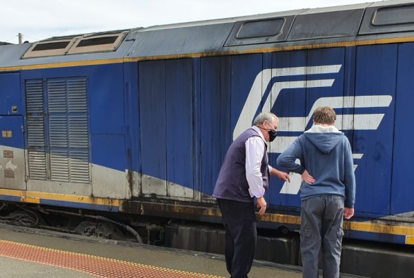 Year 9 student and community mentor looking at trains at Benalla station